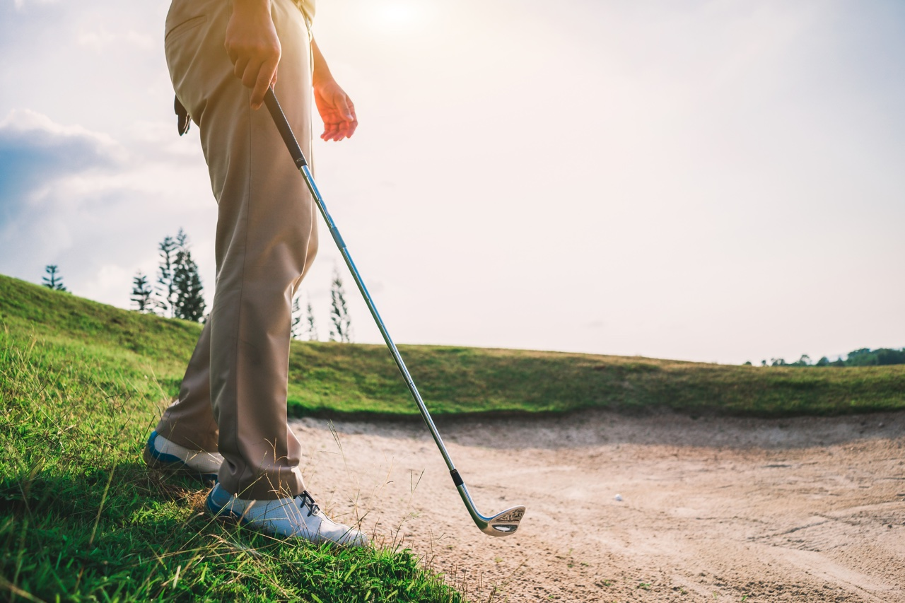 Golfer enters a bunker with a wedge