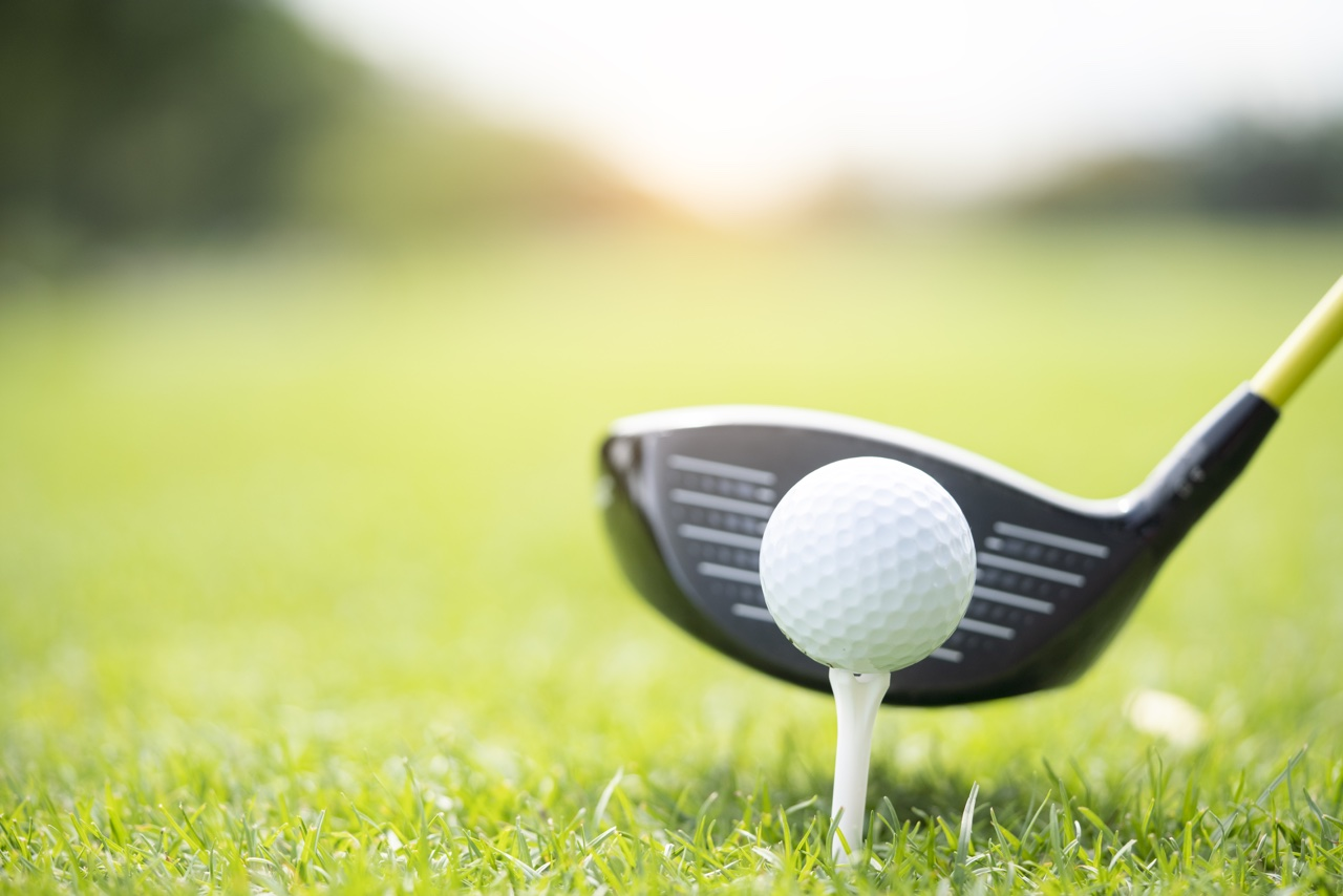 A driver hovers behind a teed up ball