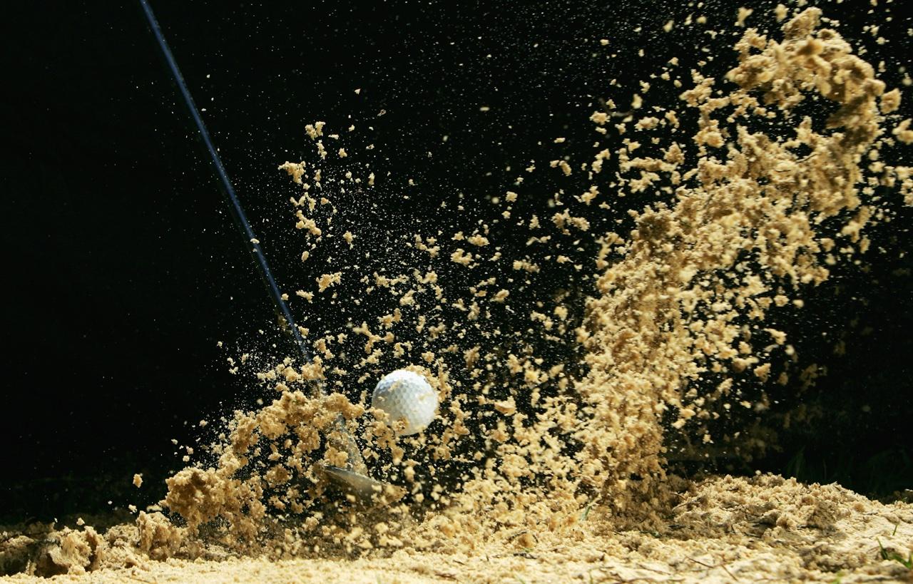 golf club hitting a bunker shot