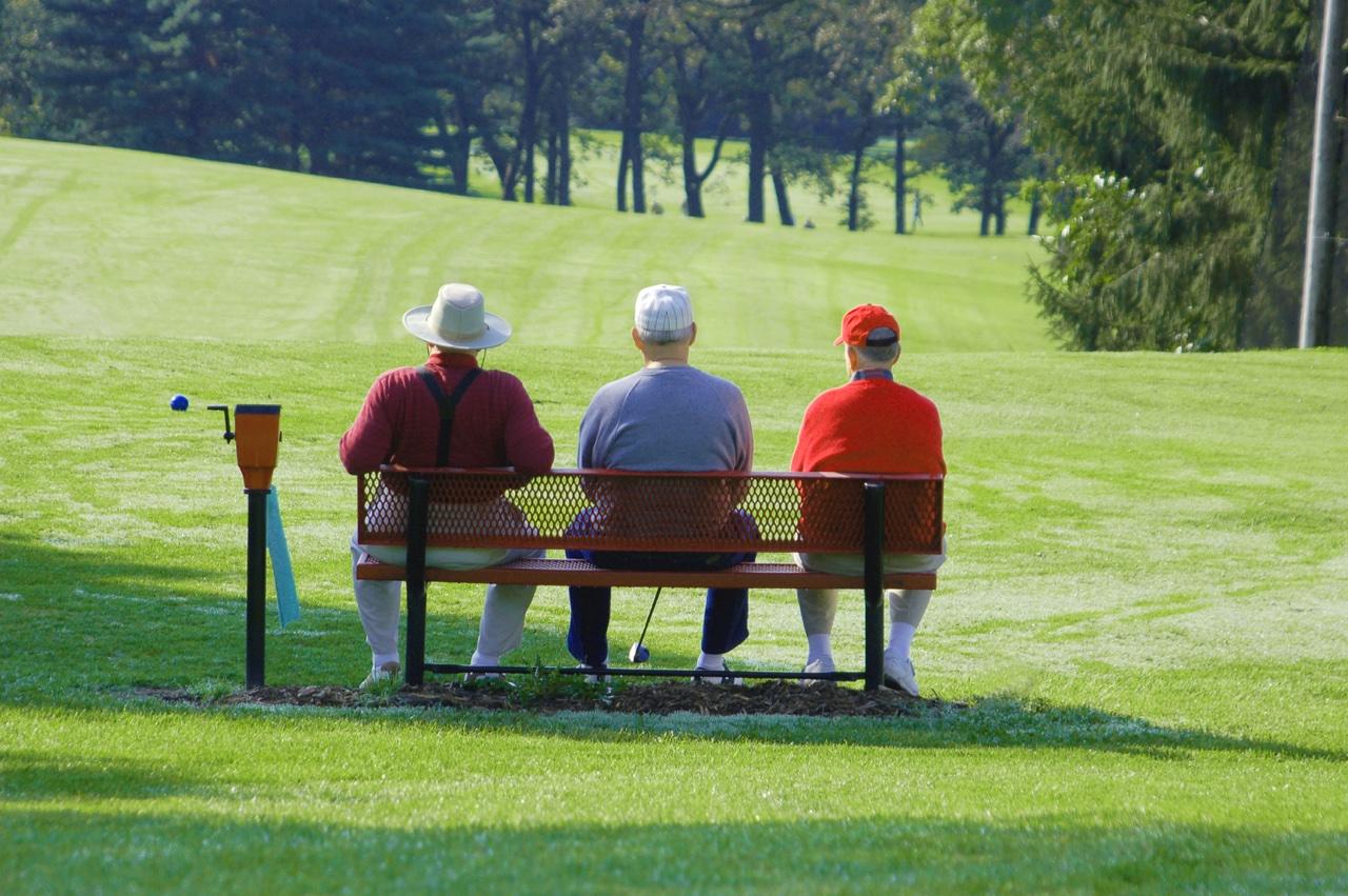 Three golfers wait on a bench
